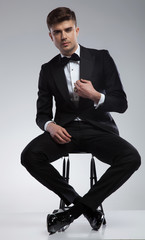 sexy seated elegant man fixing black suit collar