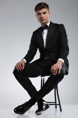 handsome man in tuxedo resting on metal chair