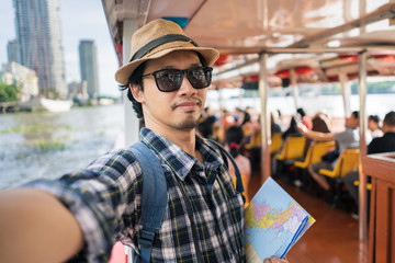 Asian man bag pack tourist take a selfie in travelling at Thailand .