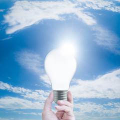 hand holding a light bulb on blue sky background