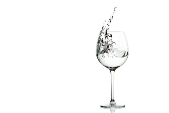 Clear water splashing in the wine glass. horizontal with space for text