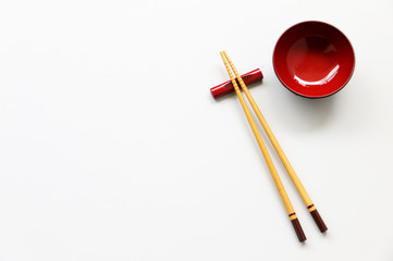 wood chopsticks and red bowl on White table background.Flat lay,Copy space