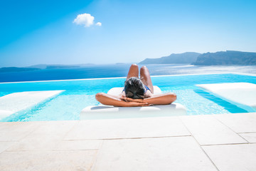 woman at an infinity pool looking out over the caldera of  Santorini Greece, luxury vacation