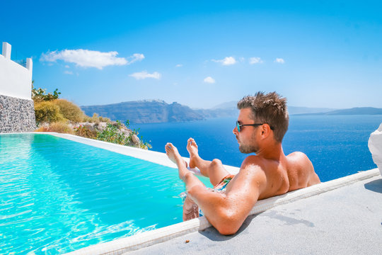 young man on vacation Santorini Greece by the swim pool looking out over the sea