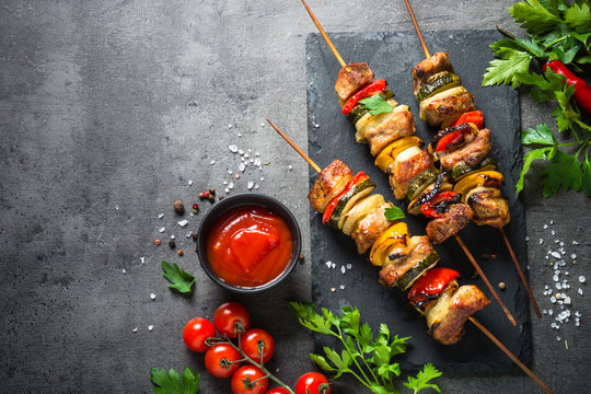 Grilled shish kebab with vegetables  on black.