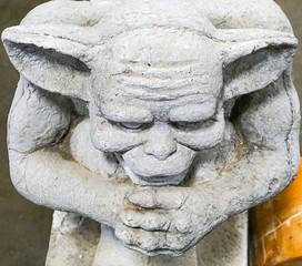 A concrete statue of a garden Gargoyle