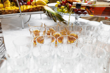 Close up of barman hands pouring whiskey in crystal glasses