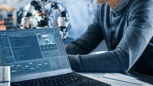 Robotics Engineer Manipulates Voice Controlled Robot, Laptop