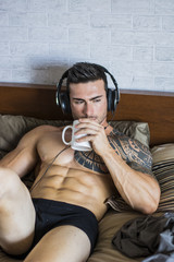 Shirtless muscular sexy male model listening to music on headphones and drinking tea or coffee, lying alone on bed in his bedroom, relaxing with coffee or tea cup