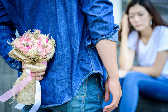 Asian man has preparing and waiting with flower for say sorry and apologies to girlfriend.