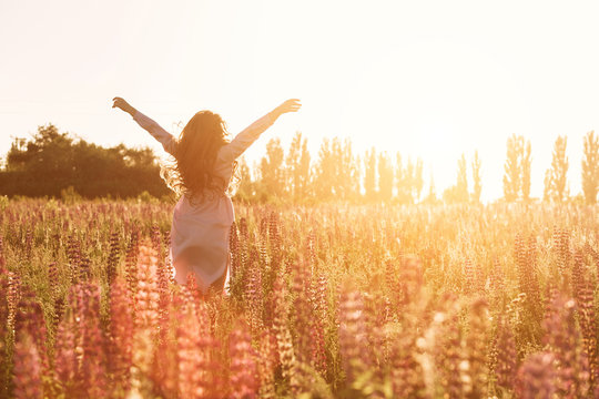 Happy woman in green flower field raised hands to sky. Warm soft sunset light