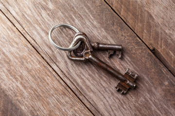 old keys on a brown wooden background