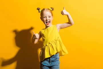 Girl with red hair on a yellow background. The girl laughs and shows the class sign.