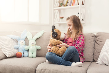 Little girl and teddy bear listening to music