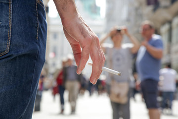 Close up image of young man smoking a cigarette on the street
