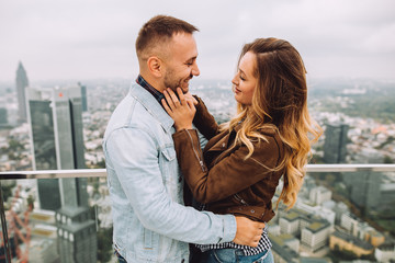 Young couple in love embraces on the roof of a skyscraper in Germany.