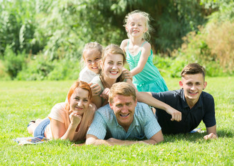 Smiling man and woman with kids lying in park