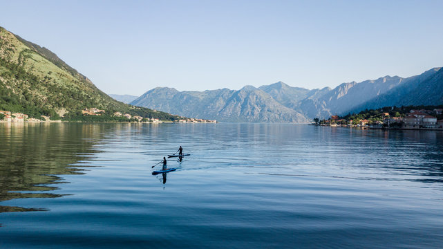 Aerial  view of 2 men crosses the bay using the paddleboard or sup board in turquoise tropical clear waters in Montenegro