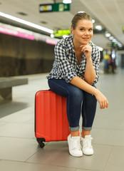 Girl sitting on suitcase at metro station
