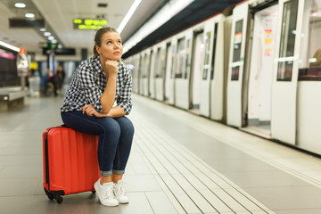 Girl sitting on suitcase at metro station
