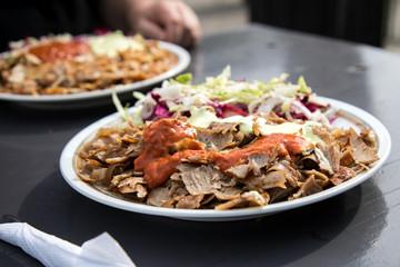 Mann isst Kalbfleisch Dönerteller mit Salat und Sauce