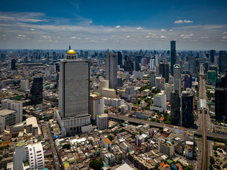 Wall Mural - Aerial view of Bangkok skyline and skyscraper with BTS skytrain Bangkok downtown. Panorama of Sathorn and Silom business district Bangkok Thailand with blue sky and clouds.