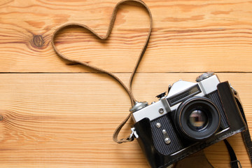Old vintage camera on a wooden table. Heart shape