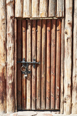 An ancient wooden door in a wooden wall. The door is closed with an iron latch and a lock