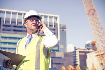 Man architector outdoor at construction area having mobile conve