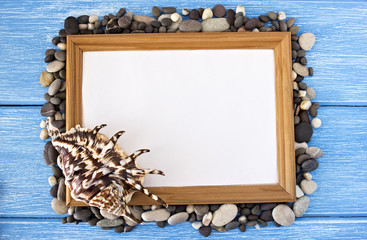 Frame of pebbles and shells on a blue wooden background