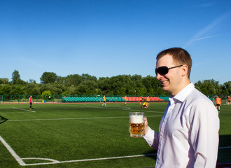 A man in black glasses is drinking beer from a glass in the background of the stadium where they play football, a football match and drinking beer