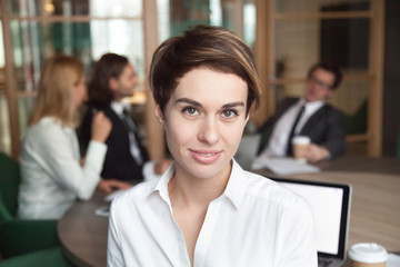 Smiling female office worker looking at camera, making headshot photo for company business catalogue, positive woman in formal wear posing at corporate meeting. Concept of leadership, confidence.