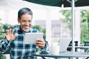 Mature asian man waving hand with smiling and enjoy using tablet making video call to child, grandchild or friends at outdoor coffee shop. Elderly people with smart technology meeting online concept.