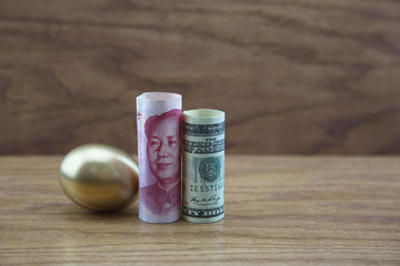 Gold nest egg with Chinese and American currency against wood background