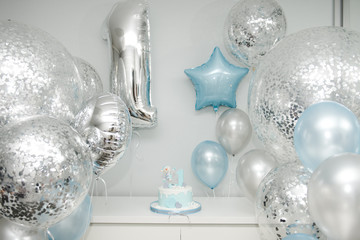Colorful decoration of a first year birthday cake. Baby cake smash. Birthday cake for 1 year old boy. A lot of balls and cake. Birthday party in blue and silver.