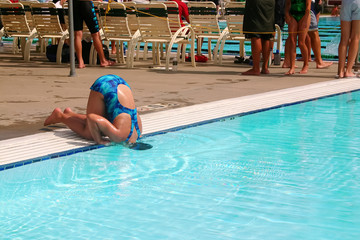 Humorous image of a girl in bathing suit cooling her head  in a pool
