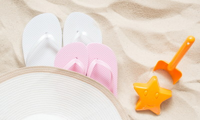 Beach hat and flip flop. Bright plastic children's toys on the sand. The concept of a beach holiday for children. Summer concept. Flat lay, top view, copy space