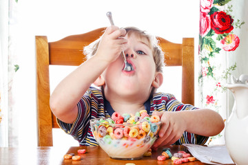 Boy eating colorful breakfast cereal