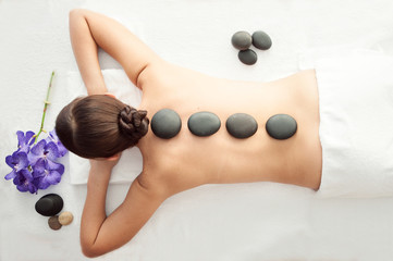 Stone treatment. Top view of beautiful young woman lying on front with spa stones on her back. ...
