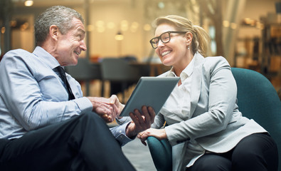 Smiling businesswoman shaking hands with a colleague in an offic