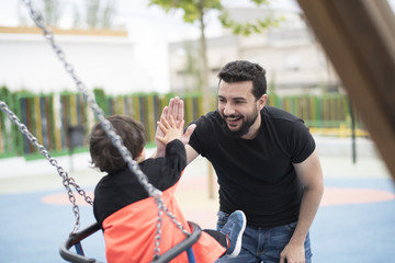 little boy having fun swinging at the park, hi five with his father