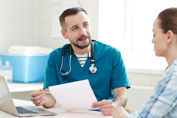 Young doctor with paper explaining something to patient and giving advice