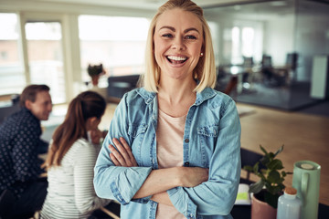Laughing young businesswoman with colleagues working in the back