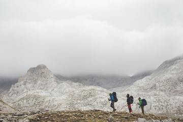 Silhouette of three mountaineers walking on the path in a row on a cloudy day