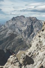 Far view of a hiker in the top of a rock in a scenic landscape in Picos de Europa National Park, Spain