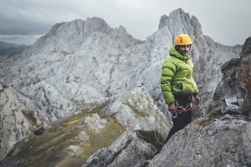 Portrait of mid aged mountaineer standing on the top of a rocky mountain wearing a helmet