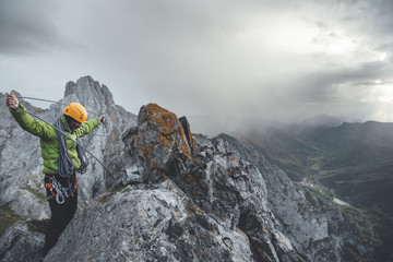 Mid aged climber bundle a rope on the top of a rocky mountain wearing a helmet