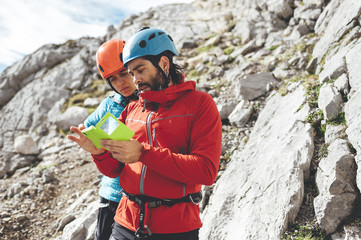 Couple of climbers using mobile phone to send a message wearing helmets and harness before climbing