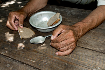 Hands the poor old man's, piece of bread and empty bowl on wood background. The concept of hunger or poverty. Selective focus. Poverty in retirement.Homeless. Alms