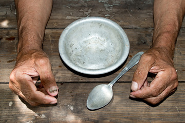 hands the poor old man's and empty bowl on wood background. The concept of hunger or poverty. Selective focus. Poverty in retirement.Homeless.  Alms Fotomurales
